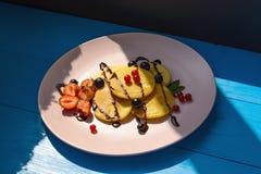 Pancake rubicondo con le bacche nei raggi luminosi del sole di mattina Fotografie Stock Libere da Diritti