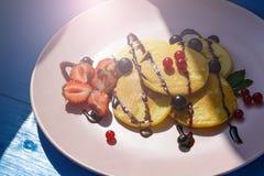 Pancake rubicondo con le bacche nei raggi luminosi del sole di mattina Fotografia Stock