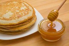 Pancake russi con miele su una tavola di legno Immagini Stock