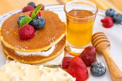 Pancake serve with ice cream honey and fruits. On white plate Royalty Free Stock Photo