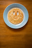 Pancake with smiley face on plate Royalty Free Stock Photo