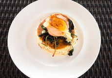 Pancake with smoke salmon, spinach and egg. Pancake with smoke salmon, spinach and poached egg on white plate Royalty Free Stock Image
