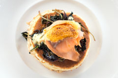 Pancake with smoke salmon, spinach and poached egg. On white plate Royalty Free Stock Photo