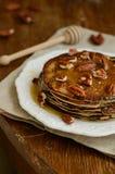 Pancake sottili casalinghi con miele e le noci americane su porcel bianco Fotografia Stock Libera da Diritti