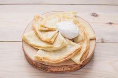 Pancake sottili russi su un supporto di legno fatto di legno naturale con panna acida Maslenitsa è un festival dell'alimento di M fotografia stock