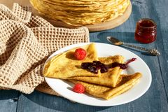 Pancake sottili su una tavola blu e su un piatto Fotografia Stock