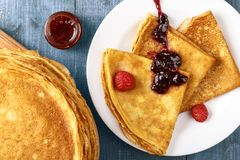 Pancake sottili su una tavola blu e su una vista superiore del piatto Immagini Stock Libere da Diritti