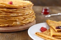 Pancake sottili su una tavola e su un piatto Fotografie Stock