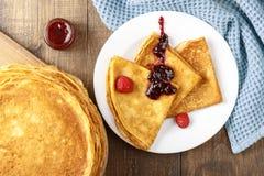 Pancake sottili su una tavola e su un piatto Fotografia Stock