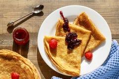 Pancake sottili su una tavola e su una vista superiore del piatto Immagine Stock