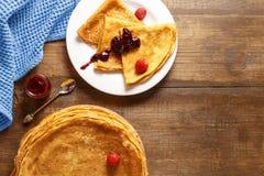 Pancake sottili su una tavola e su una vista superiore del piatto Immagini Stock Libere da Diritti