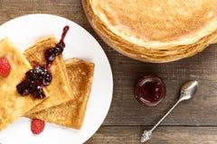 Pancake sottili su una tavola e su una vista superiore del piatto Immagini Stock