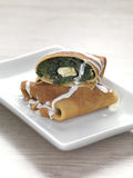 Pancake with spinach and cheese. A pancake filled with cooked spinach and feta cheese stock photos