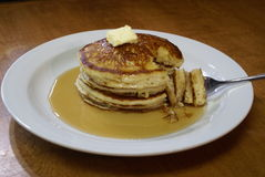 Pancake Stack 2. Light and fluffy stack of three pancakes covered in maple syrup and a pat of butter Stock Images