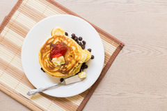 Pancake stack with strawberry jam on wooden background Royalty Free Stock Images