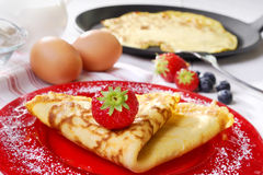 Pancake with strawberries. On a plate and a pan and ingredients in the background Royalty Free Stock Image