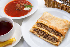 Pancake stuffed with meat and borsch with greenery Stock Images