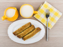 Pancake stuffed in white dish, cup milk, napkin and fork Stock Photography
