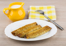 Pancake stuffed in white dish, jug milk, napkin and fork Royalty Free Stock Photos