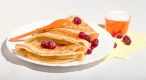 Pancake su un piatto bianco, con le bacche di un mirtillo rosso e di una crema Immagine Stock Libera da Diritti