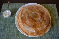 Pancake su un piatto e su una panna acida in un incavo immagini stock libere da diritti