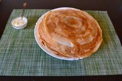 Pancake su un piatto e su una panna acida in un incavo immagine stock libera da diritti