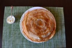 Pancake su un piatto e su una panna acida in un incavo fotografia stock