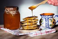 Pancake su un piatto, su una brocca di latte ceramica e su un miele Fotografia Stock