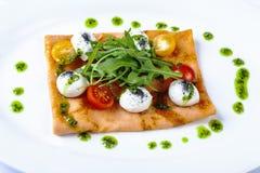 Pancake with tomato and Arugula. With matsarella royalty free stock images