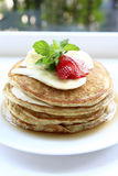 Pancake Tower. A four layers pancake. Each layer fills with fresh banana. The pancake topping with fresh strawberry and banana and mint leaf Royalty Free Stock Images