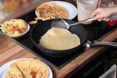 Pancake is turned. A pancake is lifted out of the pan in order to turn it around. in the foreground and background ready made pancakes are to be seen Royalty Free Stock Photos