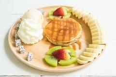 Pancake with vanilla ice-cream and fruit. Pancake with vanilla ice-cream ,whipped cream, bananas, kiwi strawberry, dragon fruit and honey Royalty Free Stock Photos