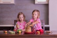 Pancake week. Little girls (sisters) eat pancakes. Stock Images