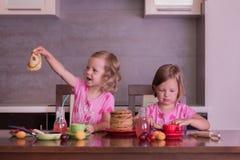 Pancake week. Little girls (sisters) eat pancakes. Royalty Free Stock Photography