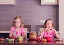 Pancake week. Little girls (sisters) eat pancakes. Stock Photo