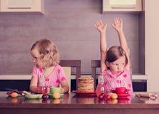 Pancake week. Little girls (sisters) eat pancakes. Royalty Free Stock Images