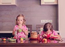Pancake week. Little girls (sisters) eat pancakes. Royalty Free Stock Image