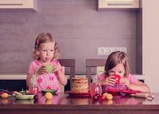 Pancake week. Little girls (sisters) eat pancakes. Stock Image