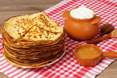 Pancake week. Pancakes, honey and a pot with sour cream. Stock Photo