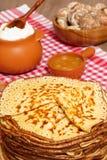 Pancake week. Pancakes, honey and a pot with sour cream. Stock Photos