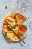 Pancake week. Thin pancakes with honey on the kitchen table. View from above stock image
