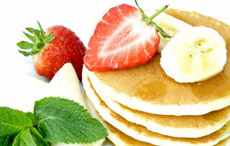 Pancakes. Stack of pancakes with banana slices, strawberries, maple syrup and mint leaves Stock Photos