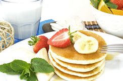 Pancakes. Stack of pancakes with banana slices, strawberries, maple syrup and mint leaves, decorated with a glass of milk, a white flower and bowl with fresh cut Stock Photo