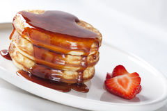 Pancakes. Covered in syrup with fresh strawberries Stock Photo