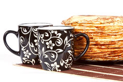Pancakes. Cups with tea and a pile of pancakes on a plate Royalty Free Stock Image