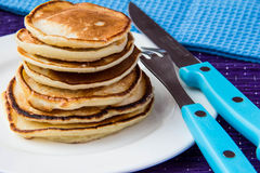 Pancakes. On white plate with blue fork and knife Stock Photo