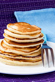 Pancakes. On white plate with blue fork Stock Photos