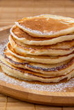 Pancakes. On a wooden plate with sugar powder Royalty Free Stock Photography