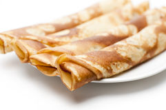 Pancakes. Rolled pancakes on a white plate with white background Royalty Free Stock Image