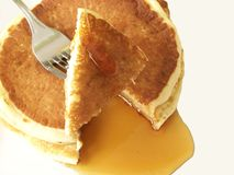 Pancakes. Image of two sliced pancakes and metal fork, with a stream of maple syrup Royalty Free Stock Images